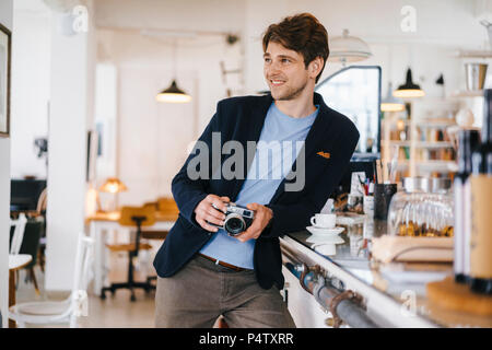 Smiling man in a cafe holding camera