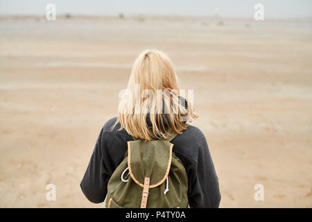 Back view of blond young woman with backpack on the beach - Stock Photo