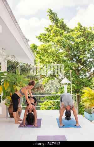 Yoga instructor teaching woman correct yoga pose on terrace - Stock Photo