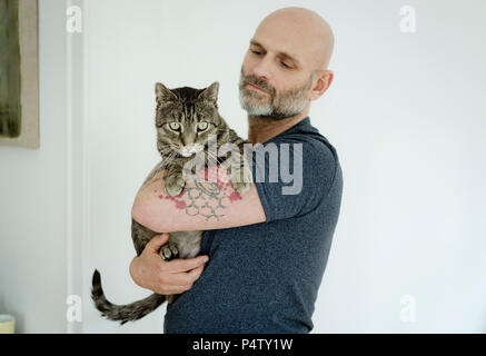 Tattooed man carrying his cat - Stock Photo