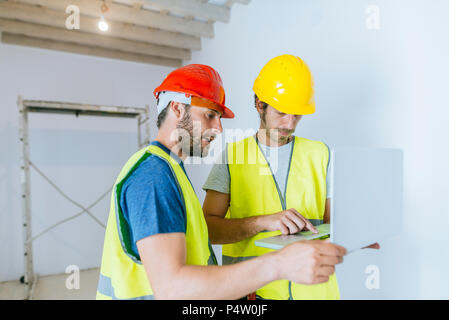 Workers using laptop at construction site - Stock Photo