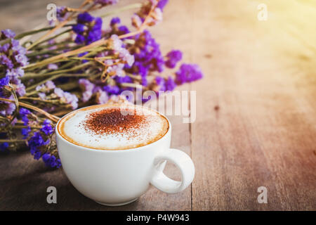 A cup of coffee with bouquet of violet dried flowers on wooden floor background,in morning sun. - Stock Photo