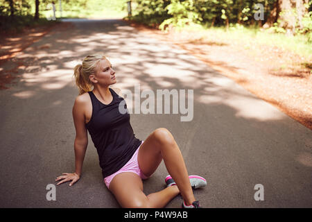 Fit young blonde woman in sportswear sitting alone on a road in a forest taking a break from a run - Stock Photo