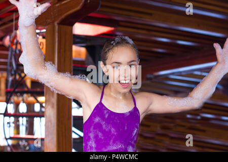Happy young girl in a soapy foam smiling at a foam party on yacht - Stock Photo