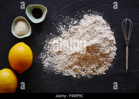 food blog making a lemon pie flour lemons on dark surface - Stock Photo