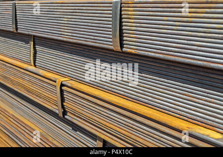 The rusty hot-rolled sheet metal in packs at the warehouse of metal products piled in the open air close-up - Stock Photo