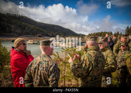 Lt. Gen. John Wissler, center, commander of U.S. Marine Corps Forces Command, speaks with Marines while overlooking an assembly area where Marine Corps Prepositioning Program Norway (MCPP-N) equipment is staged.  MCPP-N enables the rapid aggregation of a credible, agile, and flexible Marine Air Ground Task Force and creates operational and strategic options for the defense of NATO allies and partners. - Stock Photo