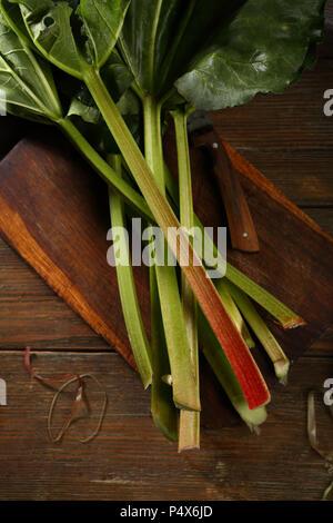Fresh Rhubarb on wooden table - Stock Photo