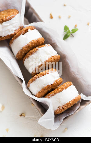 Ice cream sandwiches with nuts and wholegrain cookies. Homemade vanilla ice cream sandwiches on white background. - Stock Photo