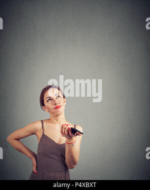 Young irritated woman using smartphone with voice recognition and looking upset with function while lookin gup - Stock Photo