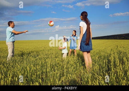 Happy family playing with ball in summer field - Stock Photo