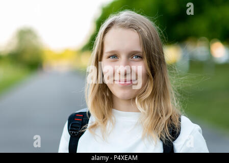A beautiful child, teenage girl. Summer in nature. Close-up portrait. Smiles happily. Free space for text. Concept of rest. Emotions of pleasure and joy. - Stock Photo