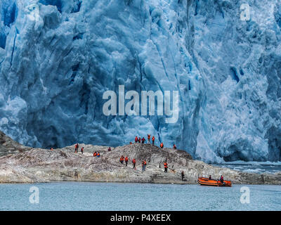 Tourists wearing life jackets explore a glacier in Torres del Paine National Park, Magallanes y de la Antartica, Patagonia, Chile - Stock Photo