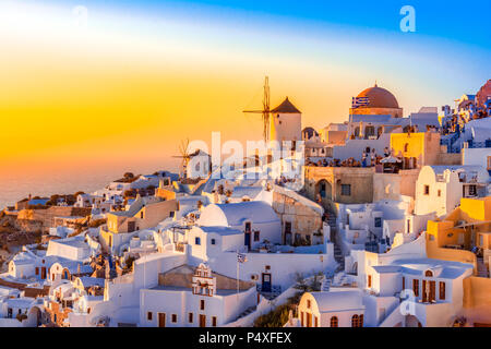 Sunset in Oia town, Santorini island, Greece. Traditional and famous white houses and churches  with blue domes over the Caldera, Aegean sea. - Stock Photo