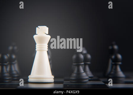 chess set on chessboard. white king against black pawn. leadership, power, hero and fight concept. selective and soft focus - Stock Photo