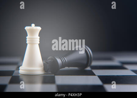 chess set on chess board. fallen black king on white queen. women power concept. selective and soft focus - Stock Photo