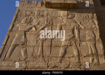 Temple of Ramses III. Relief depicting Ramses III making offerings before god Ra. New Kingdom. Thebes. Medinet-Habu. Egypt. - Stock Photo