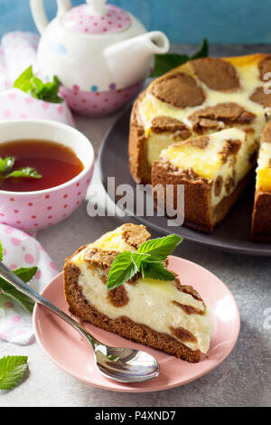 The concept of breakfast or relaxation. Chocolate New York cheesecake and mint tea cup on concrete background.