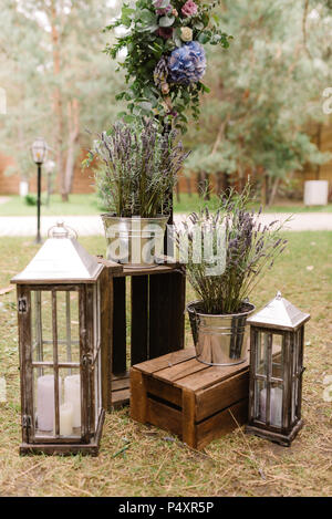 Exterior from wooden lamps and boxes. A photozone at a wedding decorated with wooden elements, greens and flowers. - Stock Photo