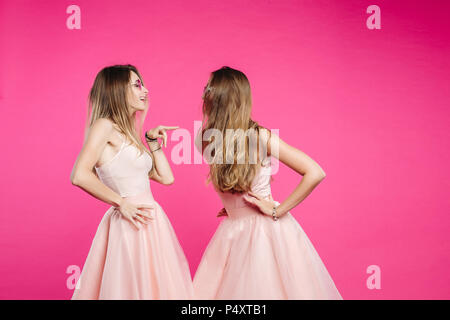 Quarrel of two sisters in pink dresses. - Stock Photo
