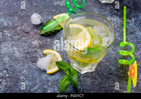 Fresh cold Mojito Cocktail with soda, ice, mint and lemon in glass and ingredients on a dark background, copy spase, selective focus - Stock Photo