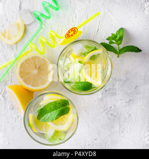 Fresh cold Mojito Cocktail with soda and lemon in glass and ingredients on a light background - Stock Photo