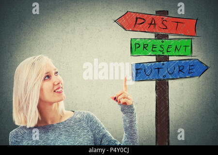 Young cheerful businesswoman pointing finger to a signpost choosing from arrows showing past, present and future. Lost in time road sign, destiny evol - Stock Photo