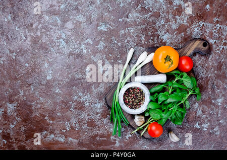 Ripe red and yellow tomatoes, green onion and basil, garlic, salt  and spices on a dark stone  background. Top view, Copy space. - Stock Photo