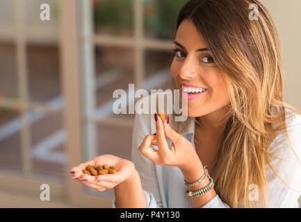 Beautiful young woman smiling and eating nuts at home. Healthy concept. - Stock Photo