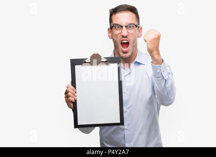 Handsome young business man showing a clipboard annoyed and frustrated shouting with anger, crazy and yelling with raised hand, anger concept - Stock Photo