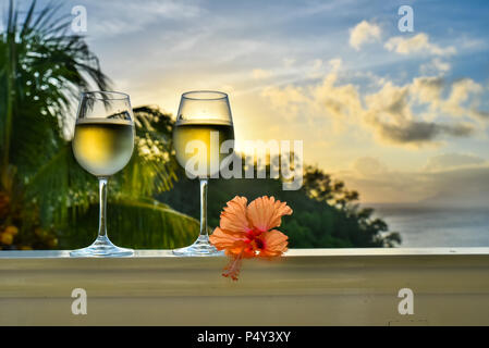 Romantic moments in summer at sunset with two glasses of white wine - Relaxing romantic holiday concept with beautiful view of tropical beach and coas - Stock Photo