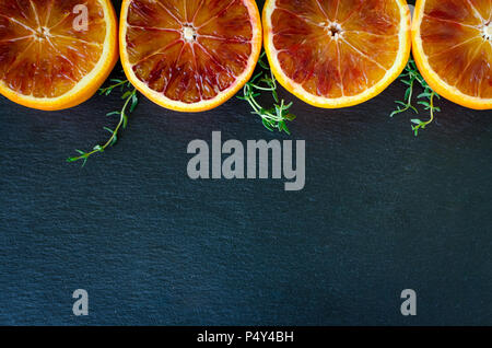 Raw of sliced blood oranges with thyme. Citrus background texture. Cut ripe juicy Sicilian Blood oganges fruits on back background. Minimalism style.  - Stock Photo