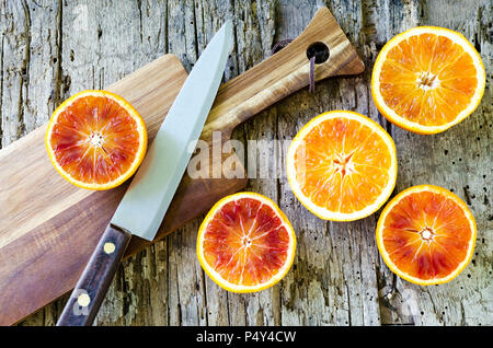 Cut blood oranges on wooden board with a knife. Citrus background. Sliced ripe juicy Sicilian Blood oranges fruits on old wooden textured background.  - Stock Photo