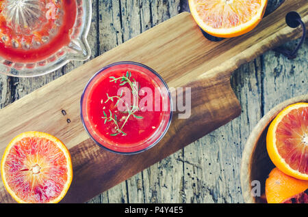 Preparation of Sicilian blood oranges juice on old wooden textured background. Freshly squeezed juice in a glass with thyme. Top view. - Stock Photo