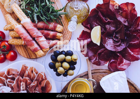 Table full of mediterranean appetizers, tapas or antipasto. Assorted Italian food set. Delicious snack on party or picnic time. Chopping board with me - Stock Photo