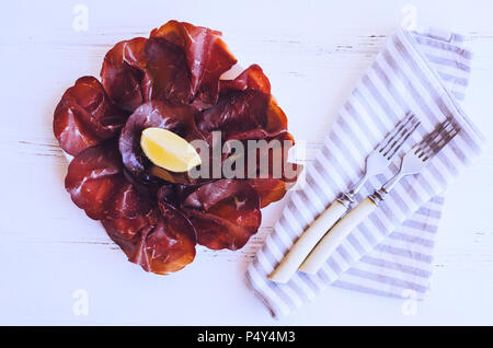 Slices of Italian meat Bresaola served with olive oil and lemon on a plate on white background. Traditional appetizers antipasti. Top view. - Stock Photo