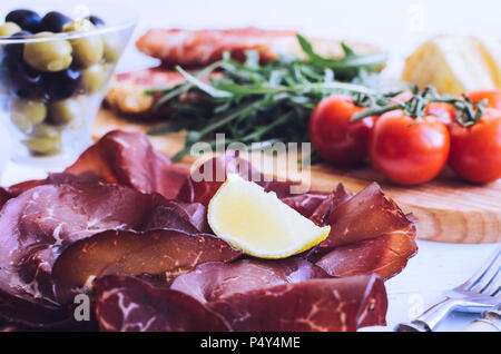 Slices of Italian meat Bresaola served with olive oil and lemon on a plate with tomatoes and bread on white background. Traditional appetizers antipas - Stock Photo