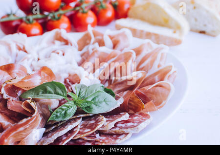 Cold smoked meat plate with pork, prosciutto, salami, bresaola and basil on white wooden background. Wine appetizer set. Italian food. - Stock Photo