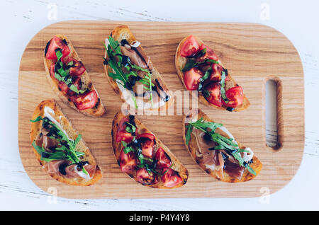 Selection of tasty Italian bruschetta or canapes on toasted baguette topped with tomatoes, Prosciutto di Parma, arugula and balsamic glasse sauce on c - Stock Photo