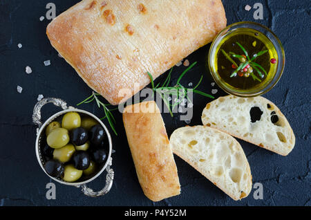 Sliced freshly baked loaf of traditional italian bread ciabatta on black stone table with rosemary, salt, olive oil and olives. Italian food concept.  - Stock Photo