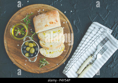 Mediterranean snacks set. Green and black olives, olive oil, herbs and sliced ciabatta bread on wooden board over dark stone background. Italian food  - Stock Photo