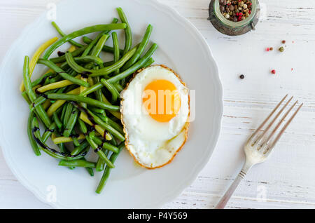 Cooked green beans with sauce balsamico glassa and fried egg in white plate on wooden background with fork. Healthy vegetarian food concept. Top view. - Stock Photo