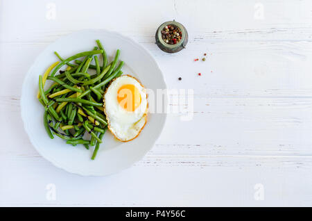 Cooked green beans with sauce balsamico glassa and fried egg in white plate on wooden background with space for text. Healthy vegetarian food concept. - Stock Photo