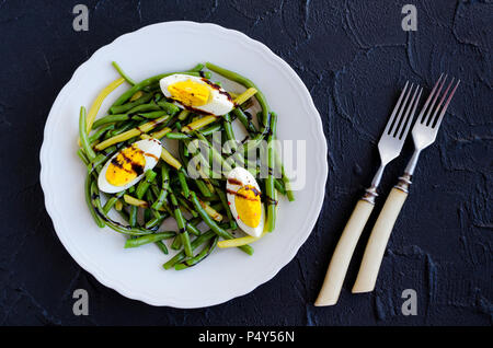 Fresh summer warm salad with cooked green beans with boiled eggs and sauce balsamico glassa in white plate on black stone background. Healthy eating.  - Stock Photo