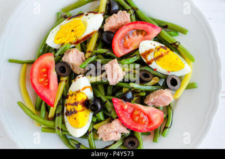 Summer warm salad with cooked green beans, tuna, tomatoes, boiled eggs and sauce balsamico glassa in white plate on wooden background. Healthy eating  - Stock Photo