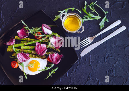 Fried egg with asparagus, tomatoes cherry, chicory and arugula in black plate on stone background with place for text. Healthy lunch concept. Deliciou - Stock Photo