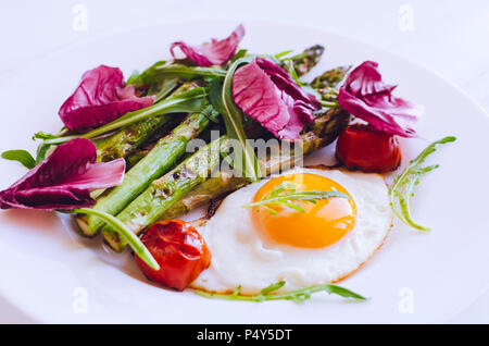 Fried egg with asparagus, tomatoes cherry, chicory and arugula in a plate on white wooden background. Healthy lunch concept. Delicious nutritious eati - Stock Photo