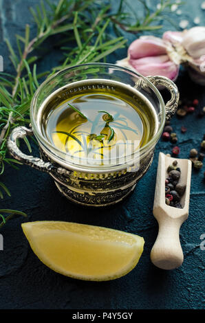 Olive oil with spices - rosemary, garlic, lemon, salt and peppercorns on dark stone table. Cooking ingredients concept. Healthy eating. - Stock Photo