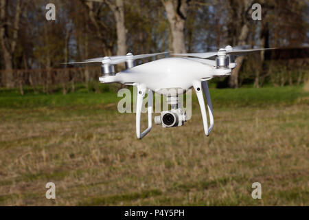 Tullgarn, Sweden - May 6, 2018: One white DJI Phantom 4 quadcopter with its camera pointing forward hovering near ground level. - Stock Photo