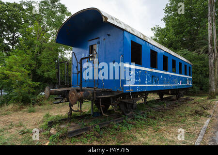 Old wooden disused narrow gauge train wagon passenger carriage in painted blue & white livery on former railway line tracks at Herceg Novi, Montenegro - Stock Photo